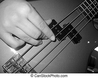 Bass Guitar - a black and white photograph of the hand of a...