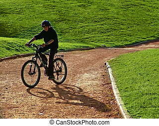 Cyclist on hillside in early summer / late spring