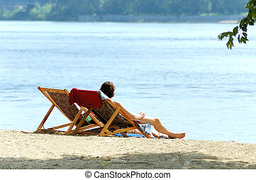 Couple on the beach - Man and woman in chairs resting on the...