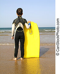 Surfer Boy - A boy, with its body board, is evaluating the...