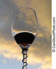 red wine - Glass with red wine against evening sky with...