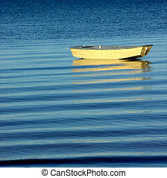 Dinghy on the Ocean - A yellow dinghy resting quietly on a...