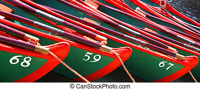 Rowing by numbers - Brightly coloured rowing boats at shore...