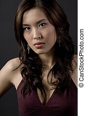 Asian Model - A serious-looking asian woman on black...