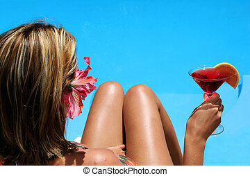 Pool Drink - Woman in bikini with cocktail by bright blue...