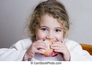 cute little girl eating a sandwich smiling to the camera