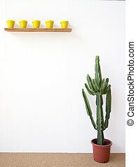 mexican scenery - little yellow pots and a huge cactus by a...