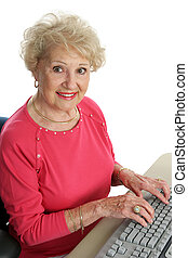 Senior @ Computer - A beautiful senior woman using the...