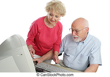 Couple On Computer - An a attractive senior couple using the...