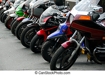 Row of motocycles parked on a street in front a motorcycle...