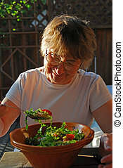 Eating senior woman - Happy senior woman in front of a bowl...