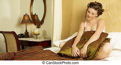 Lingerie#271 - Woman in underwear sitting on a bed.