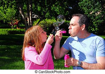 Family summer bubbles - Happy family blowing soap bubbles,...