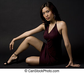 Female - An asian woman sits gracefully on the studio floor...