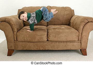 Happy Boy - Toddler boy playing on sofa.
