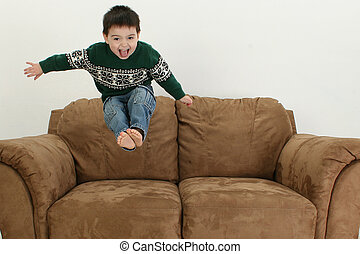 Happy Boy - Small boy jumping on couch.