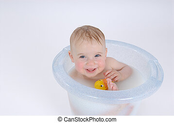 In the bathroom - One year old baby is taking a bath with...