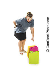 woman picking up bags - woman with back pain picking up bags...