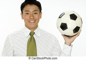 Football Business - A young businessman holding a football...