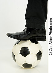 Foot Ball - A leg and smart shoe stepping on a football...