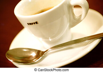 Cup of coffe - cup of coffee with tea spoon against a red...
