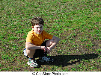 Little boy upset - Little boy sitting upset on a soccer...