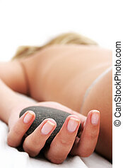 Massage - Woman with pebble in hand on massage table