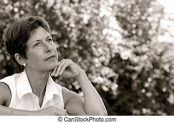Thinking - Middle aged woman sitting in a park