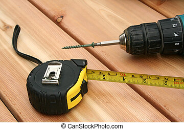 Tools - A drill and a tape measure on a new deck.