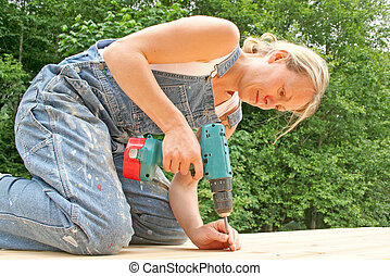 Do it yourself. - An attractive woman renovates the deck of...