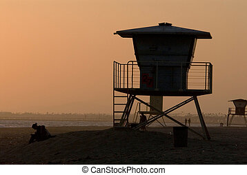 silhoette of lifeguard post at sunset