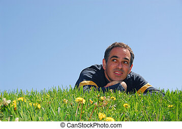 Man on grass - Man lying on grass, blue sky background