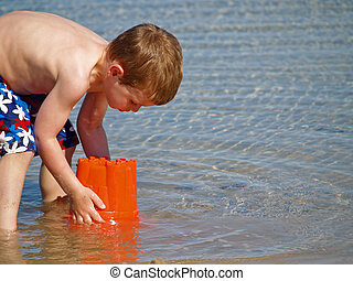 boy playing at beach - young boy playing in the water at the...