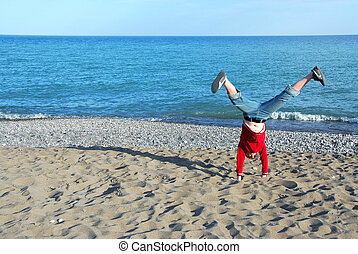 Girl doing cartwheel - Young girl doing cartwheel on a beach