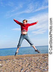 Girl child jumping - Young girl jumping on a beach