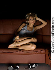 shoes off - Female in blue dress sitting on the sofa with...