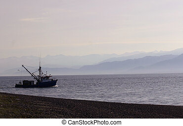 Kachemak Bay - Small boat heads out into the misty waters of...