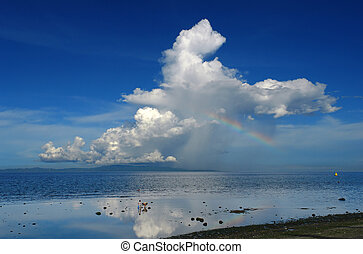 Rainbow and thunderstorm over a tropical island. - Rainbow...