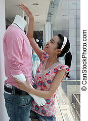 Shop assistant adjusts a mannequin - An Asian shop assistant...