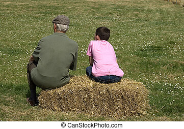 Man and boy sitting on straw bale in field. Space for text.