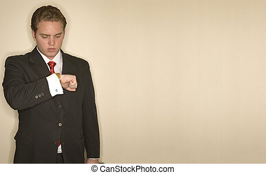 Business man checks his watch for the time as he holds his...