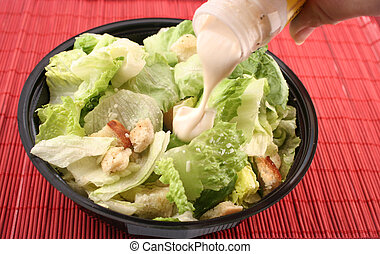caesar salad - pouring dressing over lettuce for a caesar...