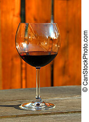 Glass of red wine on old rustic table, vertical