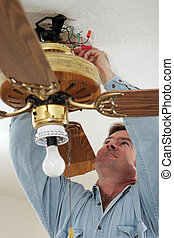 Disconnecting Fan Wires - An electrician disconnecting the...