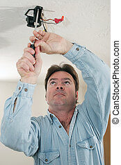 Electrician Working - An electrician unscrewing a ceiling...
