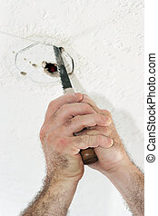 Cutting Hole For Ceiling Box - An electrician with using a...