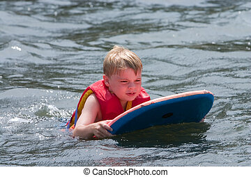 Water fun - Young boy playing in water on boogie board