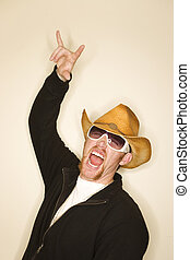 Cowboy wearing a cowboy hat having a good time with his hand...