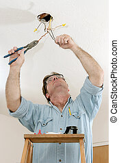 Electrician At Work - An electrician on a ladder using a...
