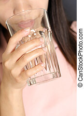 Drinking water - A woman drinking a glass of water
